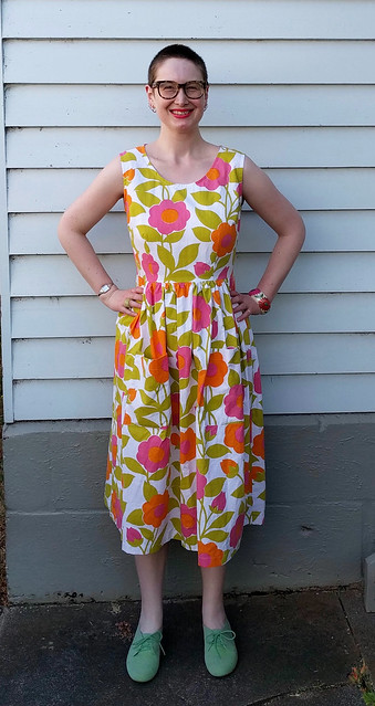 A woman stands in front of a weatherboard house. She wears a sleeveless fit and flare dress in a bright, Marimekko-style print and green flocked brogues.