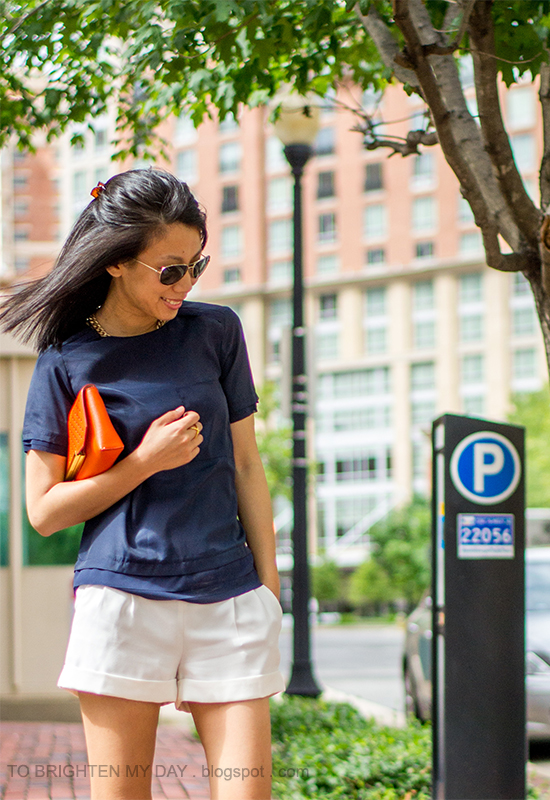 navy layered top, white pleated shorts, orange clutch