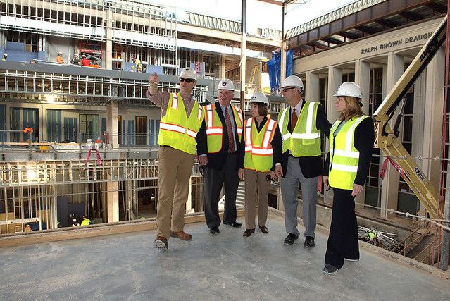 Ben Chapman leads a tour of the new Mell Classroom Building. He is pointing to a new classroom while Timothy Boosinger, Marcia Boosinger, Jim Carroll and Diane Boyd look on.