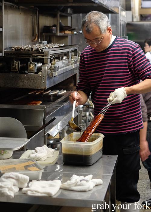 Glazing skewers of unagi eel at Nishiki Market, Kyoto