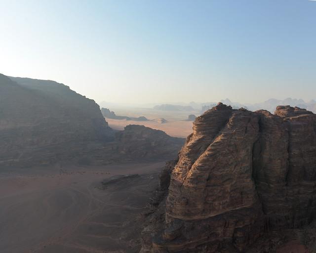 Despegando en globo entre gigantescas montañas iluminadas por el sol en Jordania