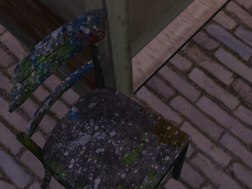 Image Description: Paint splattered chair on a brick floor.