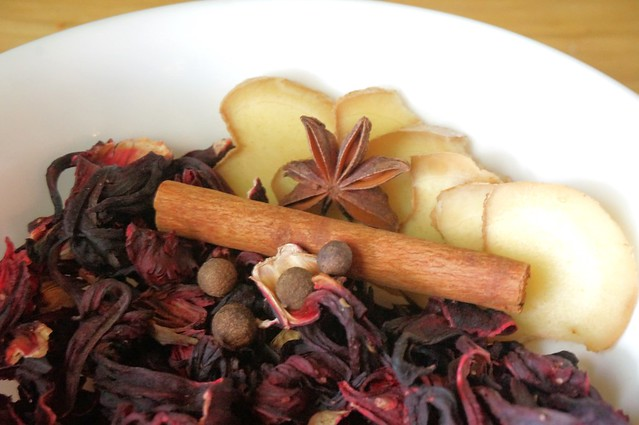 Hibiscus flowers, ginger slices, and dry spices arranged in a small white bowl like a still life