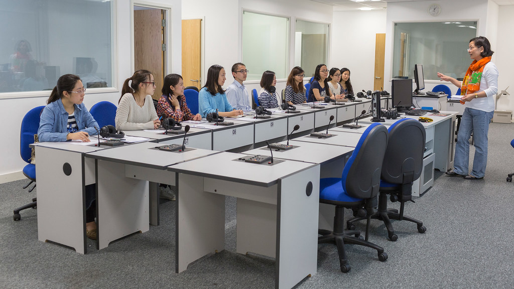 Students sitting in the interpreting laboratory listening to a lecturer.