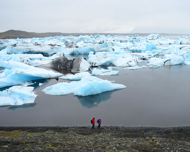 Dos personas caminando por el borde de Jökulsárlón y sus icebergs