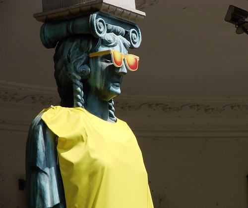Winkel van Sinkel Caryatid dressed in yellow with yellow sunglasses, ready for Tour de France