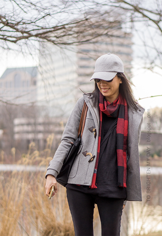 gray baseball cap, gray duffle coat with toggles, red buffalo check scarf, black fleece wrap top, black skinny jeans