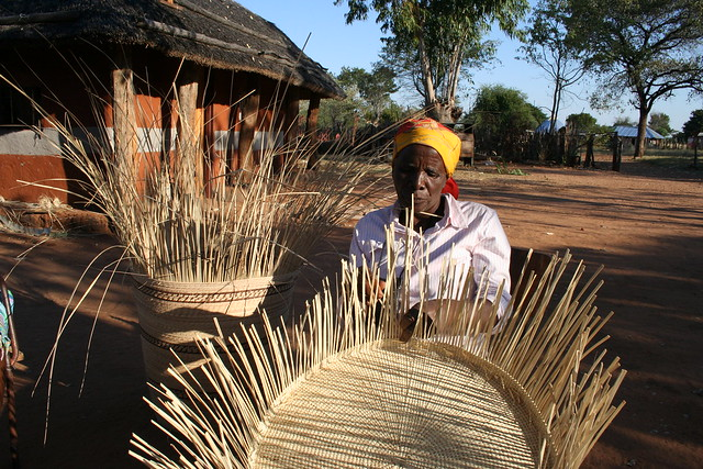 Seventy-seven-year-old Grace Ngwenya weaves a 60-cm tray. She is a member of a women's collective in western Zimbabwe that is empowering women in a drought-prone district. Credit: Busani Bafana/IPS