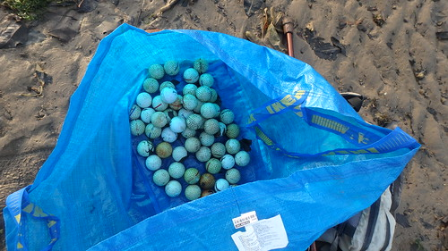 Golf balls on Berlayar Creek shore