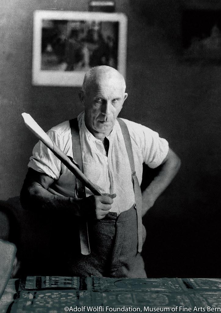 参考写真:作業机の前で紙のトランペットを持つアドルフ・ヴェルフリ(1926年頃) ベルン美術館 アドルフ・ヴェルフリ財団蔵