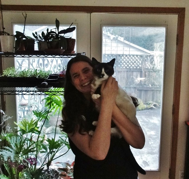 Image shows me standing with a seal-point Siamese cat in my arms. She has a white strip up her nose and is staring curiously at the camera. There is a rack of plants behind us.