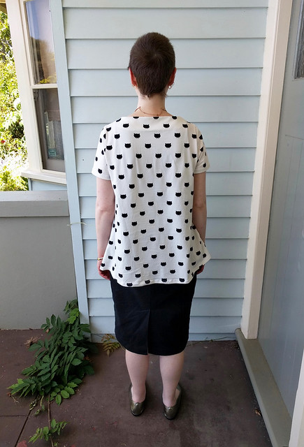 A woman stands in a veranda. She wears a white tee with black cat print, and a straight black denim skirt, with gold necklace and shoes.