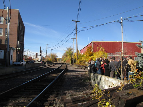 Western Ave Studios on left. Rear of Dutton St Dunkin Donuts parking lot on right. Train tracks in the middle.