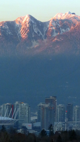 View of the sun setting on Vancouver and the North Shore Mountains from Queen Elizabeth Park in Vancouver, BC