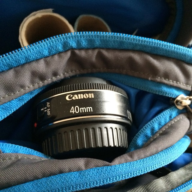 A 40mm Canon lens in a small pouch in a blue and grey backpack.