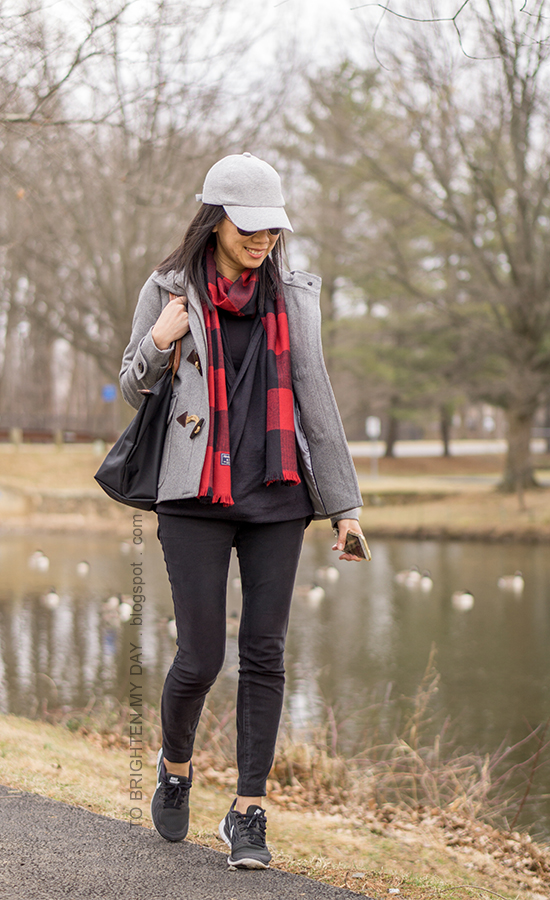 gray baseball cap, gray duffle coat with toggles, red buffalo check scarf, black fleece wrap top, black skinny jeans, black sneakers