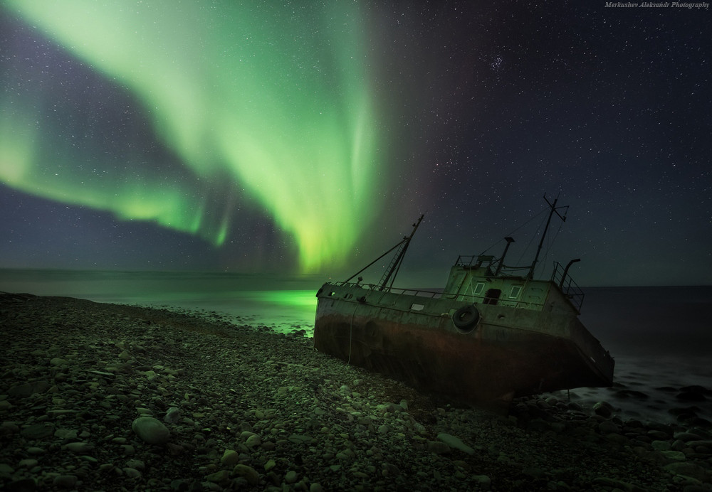 Abandoned fishing boat in the glow of the Northern Lights