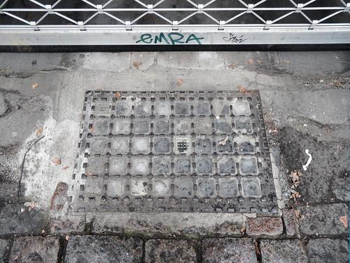"""Kellerschachtabdeckung der Firma """"Allgemeine Stern-Prismen-Gesellschaft"""" in Berlin-Kreuzberg"""