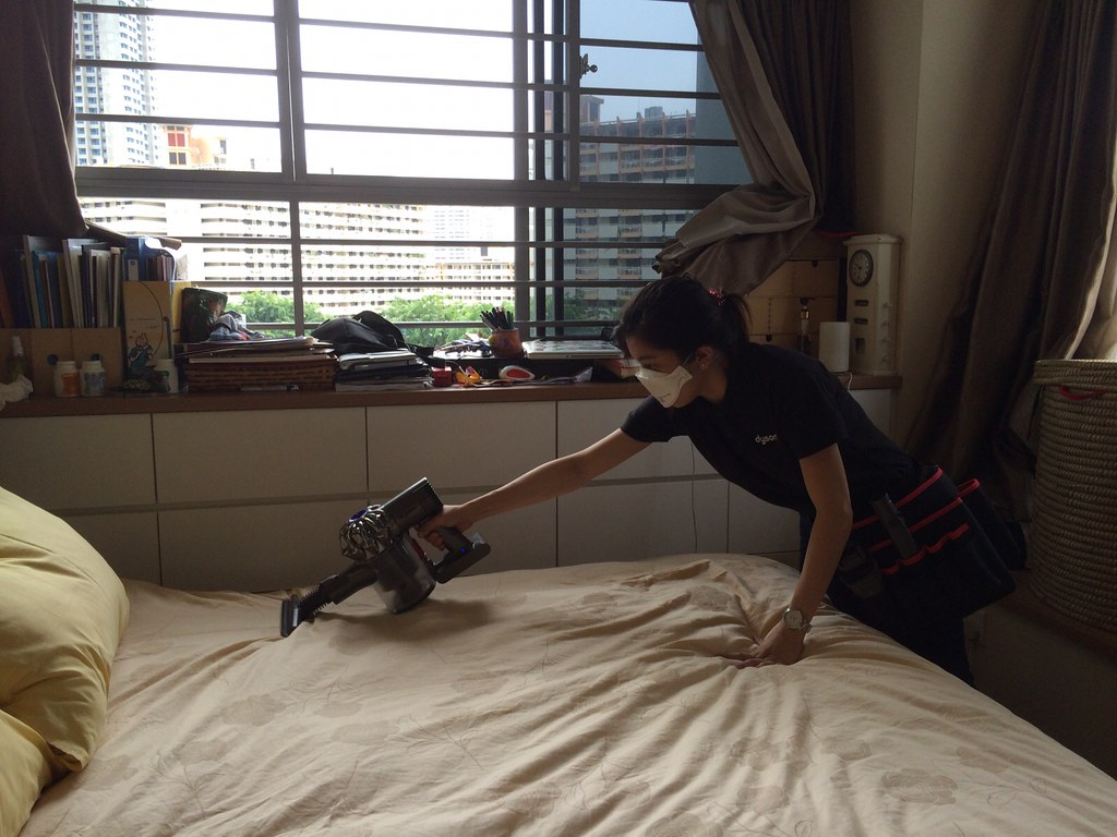 Dyson staff vacuuming the duvet for a dust sample.
