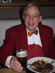 Jeg from millom wears bowtie and red jacket, toasts his meal with beer
