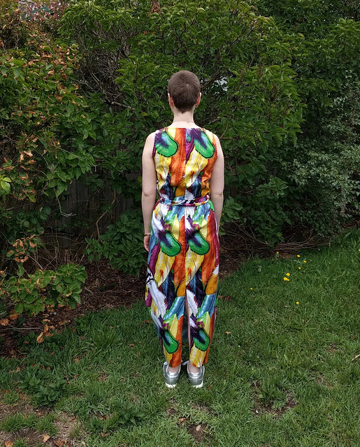 A woman stands in a garden. She wears a full length dress with ties at waist, in a colourful feather print, and silver runners.