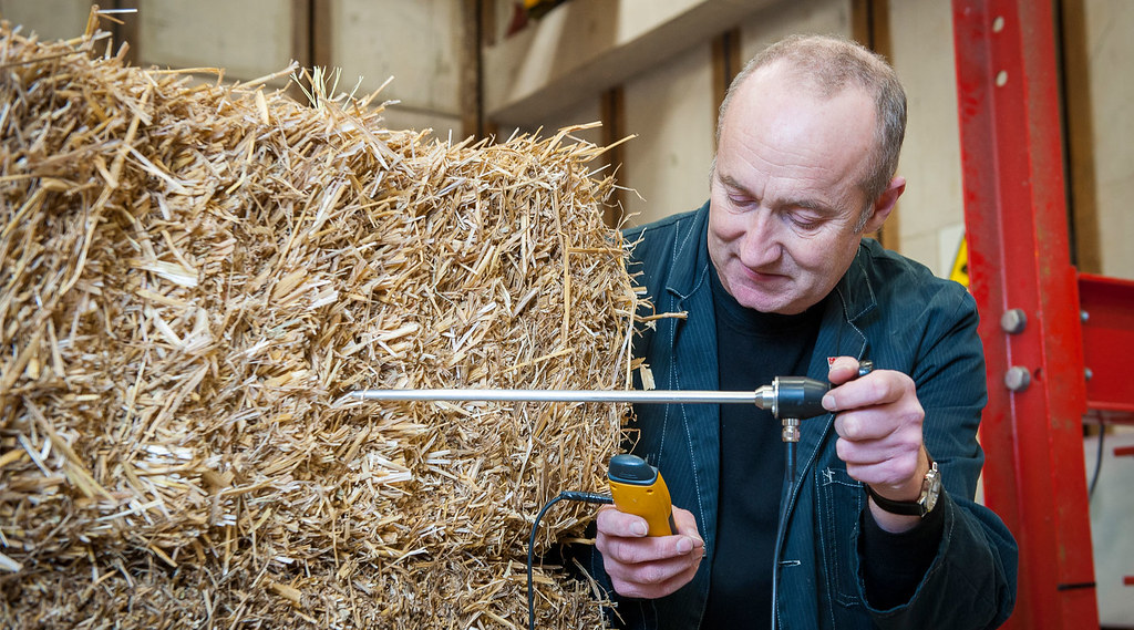 Professor Pete Walker monitors the moisture level of a straw bale