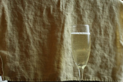 A 3/4 full glass of sparkling wine.