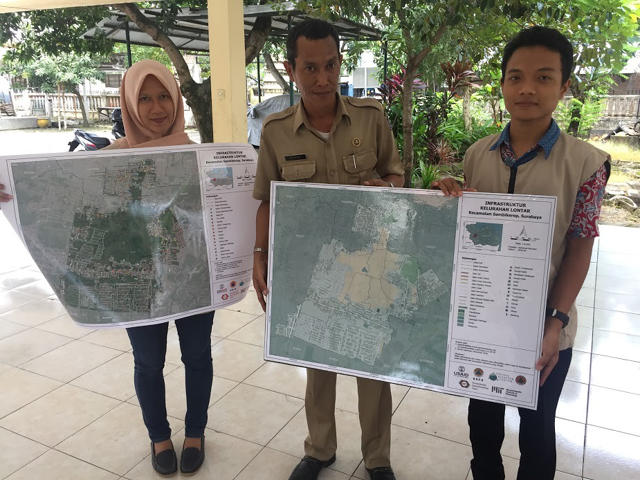 Three people holding printed maps
