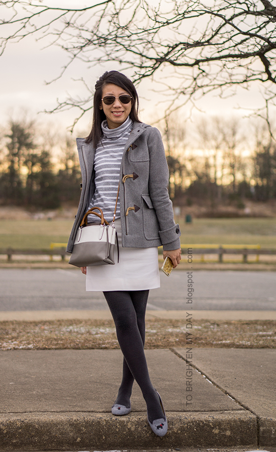 gray duffle coat with toggles, gray striped oversized turtleneck, colorblocked crossbody bag, white wool mini skirt, dark gray tights, embroidered flats with scotty dog
