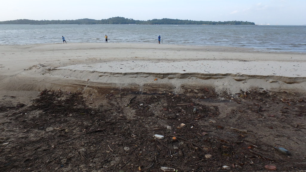 Large hole with oil on the high shore at Changi