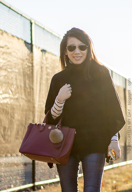black knit poncho, burgundy striped turtleneck, burgundy tote with faux fur pom