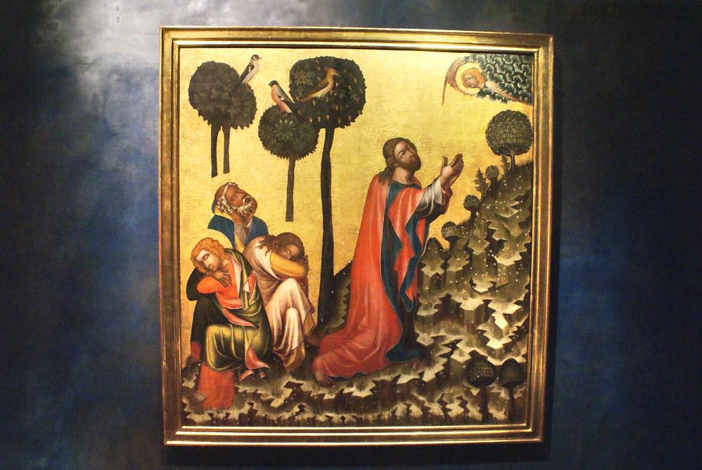 Jésus sur le mont des oliviers avec des oiseaux perchés sur des arbres isolés.