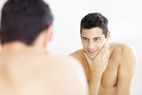 Reflection of a guy in the bathroom mirror after shaving | by InfoWire.dk