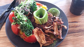 Heirloom tomatoes, avocado, almond feta, kale pesto, crispy kale, toast, mushroom bacon, rosti, poached vegan egg at Matcha Mylkbar