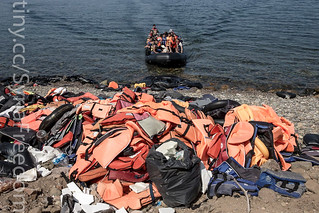 Migrants and refugees arrive by dinghy behind a huge pile of life vests after crossing from Turkey | by FreedomHouse