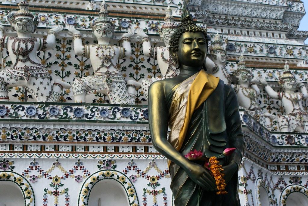 Statue de Bouddha devant la pyramide du temple Wat Arun à Bangkok.