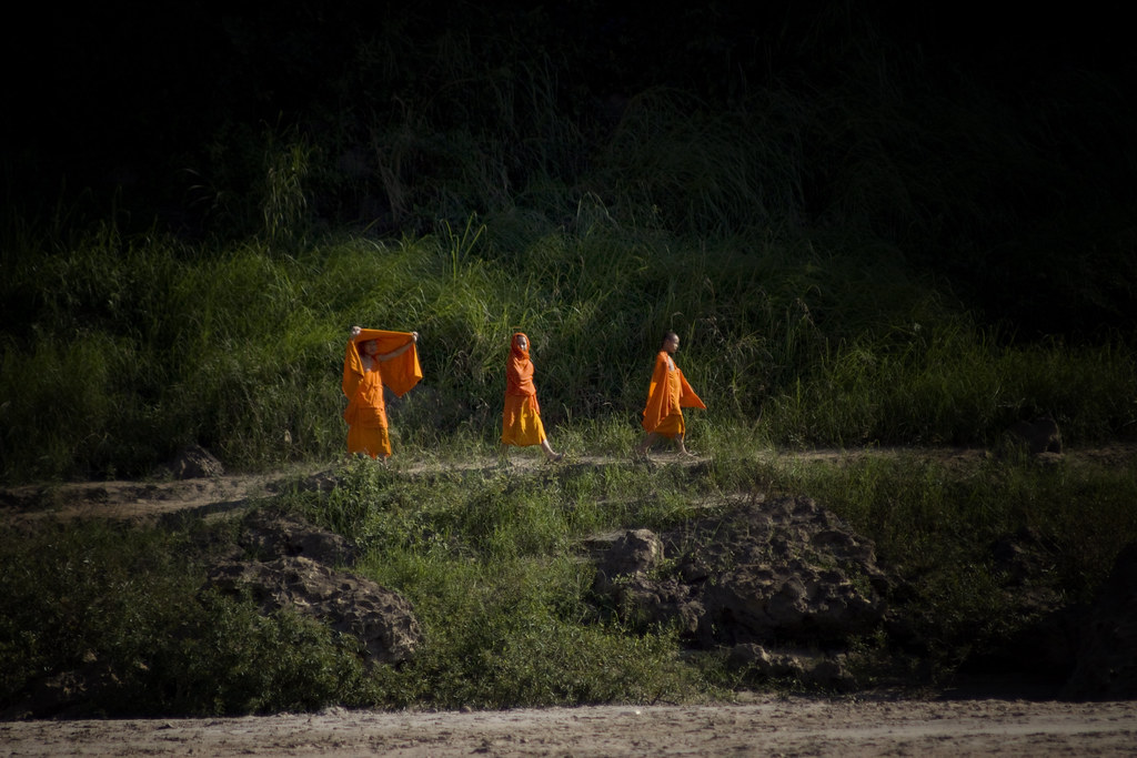 Monks Walking Along A Laotian Shore Of The Mekong