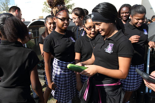 Students showing Administrator Rowe a cucumber