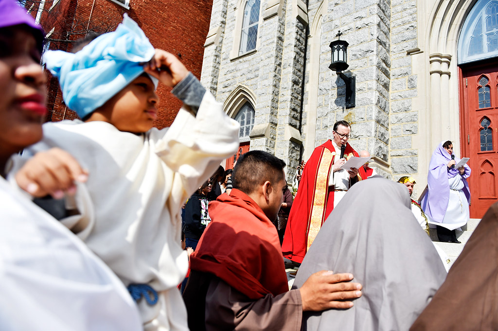 © 2016 by The York Daily Record/Sunday News. Yolequi Tejada holds her son Yaniel Calderon, 3, as she and others pray with the Rev. Jonathan Sawicki before a Good Friday street procession held by the Immaculate Conception of the Blessed Virgin Mary Church Friday, March 25, 2016, in York. The street procession followed the first nine of the 14-step Stations of the Cross, from Jesus's being condemned to death through his falling with the cross for the third time, with the remaining stations taking place inside the church. The procession was performed almost entirely in Spanish, and was followed by a Spanish-language Good Friday service.