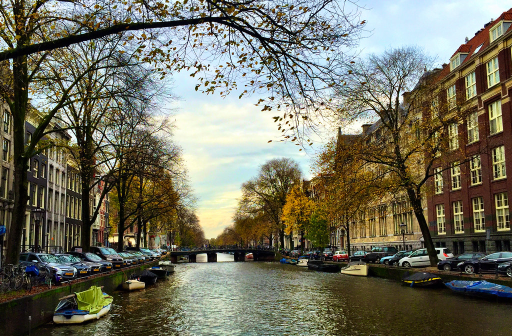 amsterdam buildings lining waterway with bridge best places to visit in europe