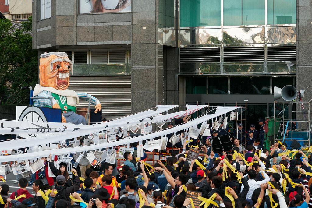 在蔡英文競選總部前,移工盟在白布幡下綁上「血汗長照」造成的悲劇新聞,讓現場群眾默哀並繫上黃絲帶。(攝影:林佳禾)