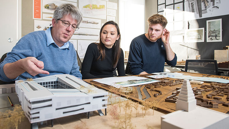 Two students around an architecture model with lecturer