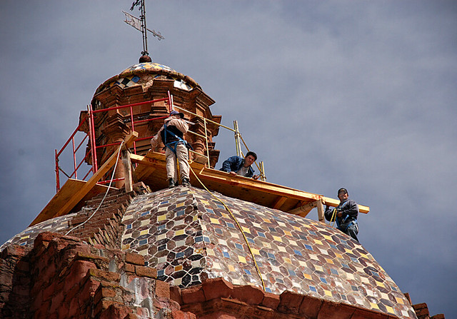 Workers wave from the tiled roof of the former San Franciscan convent in Guadalupe, Mexico