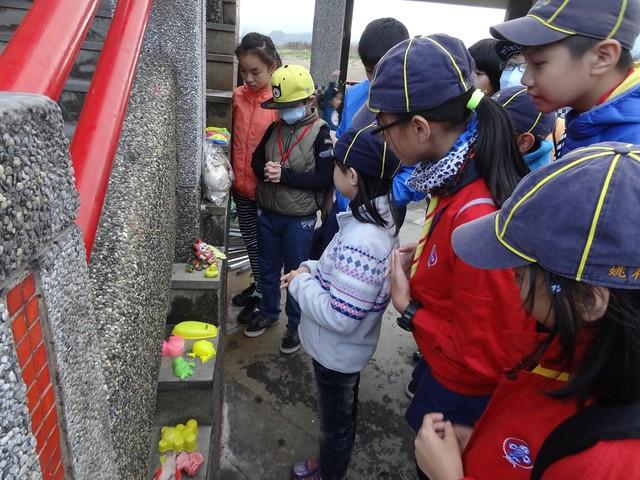 小志工們看著主辦單位過去淨灘行動中所撿來的有趣廢棄物─玩具,現場有如夜市擺攤一樣熱鬧。攝影:何沛怡