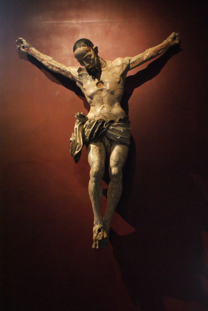 Impressionnant statue de Jésus en croix, cheveu rasé et corps meurtri.