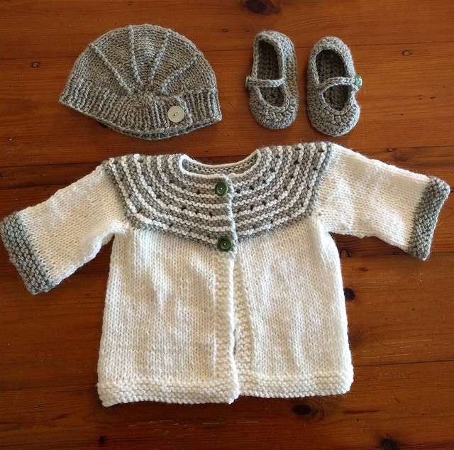 An image of a knitted layette flat on a wooden surface. Layette consists of cardigan, hat and booties, in white and green wool.