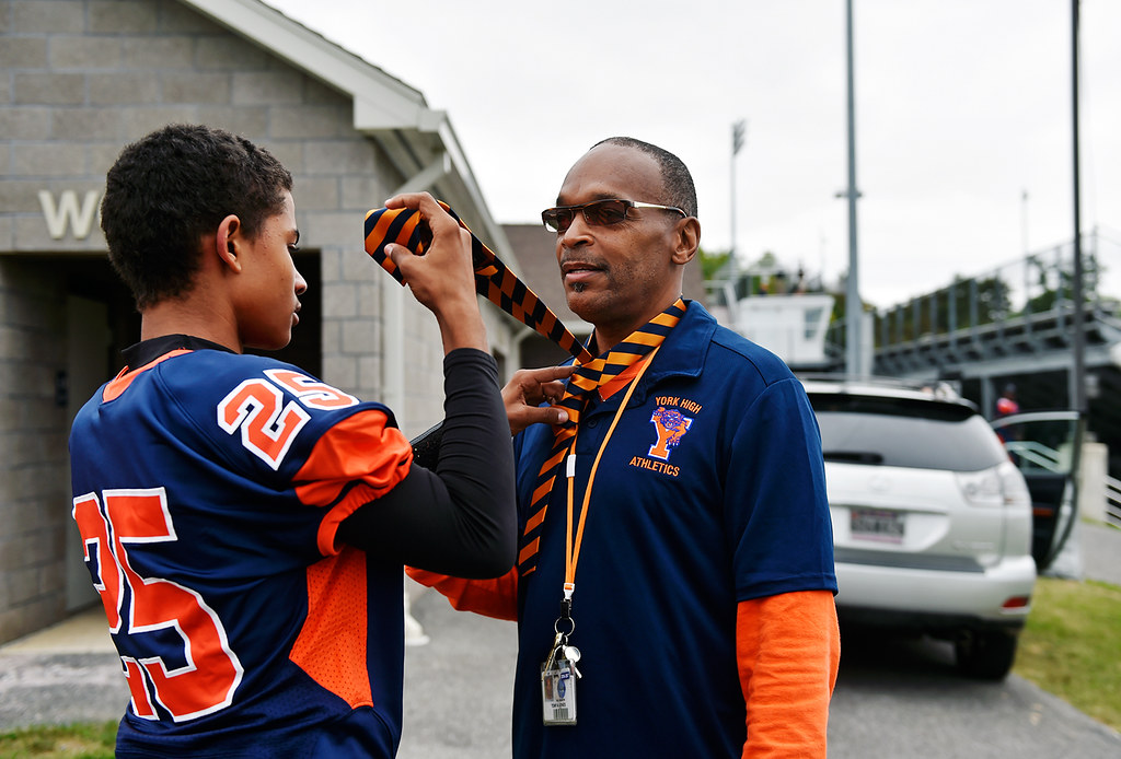 © 2016 by The York Daily Record/Sunday News. William Penn's Tobee Stokes ties a tie on track and field coach Tony Jones before a YAIAA football game Saturday, Sept. 24, 2016, at Small Field in York.