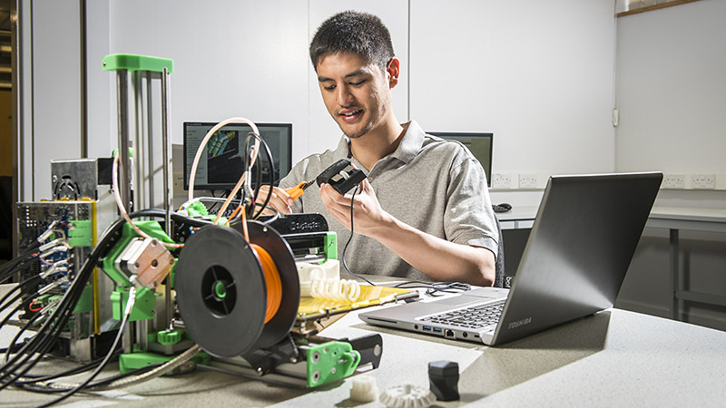 Student in laboratory works on computer mouse next to 3D printer