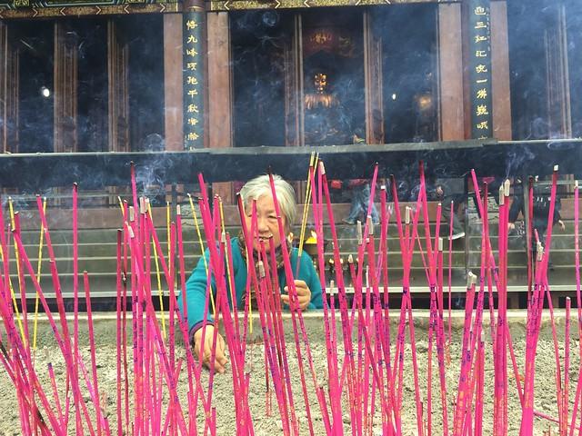 Mujer poniendo incienso en uno de los templos del Parque del Gran Buda de Leshan