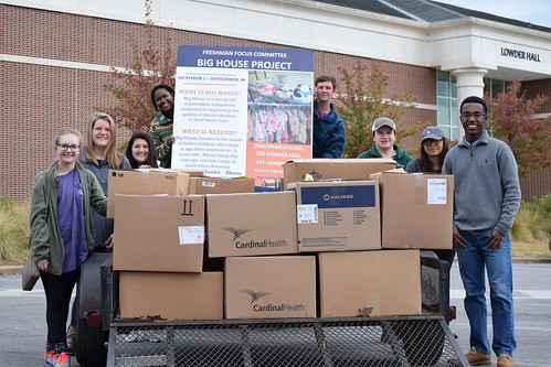 Harbert College's Freshman Focus students stand next to boxes of items gathered for local foster children.
